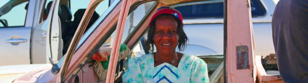 A Namibian woman wearing a hat sitting on the passenger seat of a pink car, looking out to the side