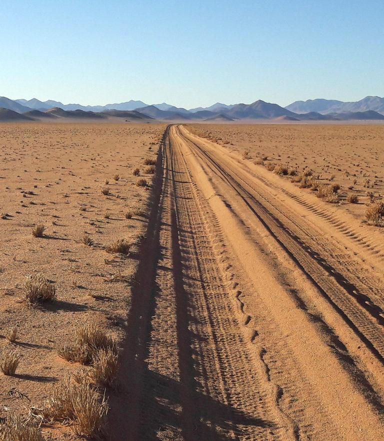 A straight, unpaved road in the desert leading to mountains in the distance